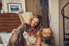 Frau, die einen Hund umarmt stockfotografie