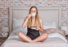 Frau, die einen Kaffee zu Hause sitzt auf Bett trinkt Lizenzfreie Stockfotos