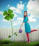 Frau, die einen Klee mit vier Blättern wässert Lizenzfreies Stockbild
