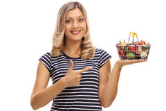 Frau, die einen kleinen Einkaufskorb und ein Zeigen hält Lizenzfreies Stockfoto