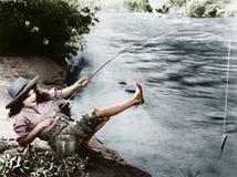 Frau, die einen kleinen Fisch fing, der über rückwärts fällt (alle dargestellten Personen sind nicht längeres lebendes und kein Z lizenzfreies stockbild