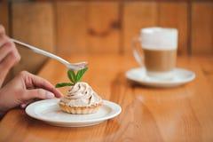 Frau, die einen Kuchen des Hüttenkäses in einer keramischen Platte mit einem Löffel auf einem Holztisch isst lizenzfreie stockbilder