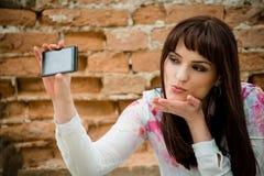Frau, die einen Kuss beim Nehmen von selfie durchbrennt Stockbild