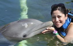Frau, die einen Kuss von einem Delphin hält lizenzfreie stockfotos