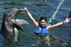 Frau, die einen Kuss von einem Delphin hält lizenzfreies stockfoto