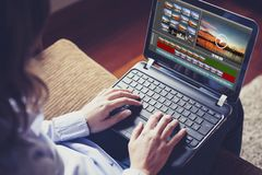 Frau, die einen Laptop verwendet, um Video beim zu Hause sitzen zu redigieren Stockbild