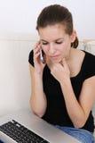 Frau, die einen Laptop verwendet und am Telefon spricht Lizenzfreie Stockbilder
