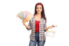 Frau, die einen Malerpinsel und ein Farbmuster hält Stockbild