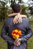 Frau, die einen Mann im Park umarmt Lizenzfreie Stockfotografie