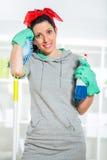 Frau, die einen Mopp und einen Spray für das Säubern hält stockbilder