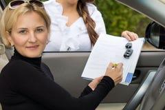 Frau, die einen Neuwagen kauft Lizenzfreie Stockfotografie