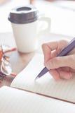 Frau, die einen Plan auf Notizbuch schreibt Lizenzfreies Stockfoto
