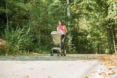 Frau, die einen Pram oder einen Kinderwagen drückt Lizenzfreie Stockfotografie