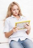 Frau, die einen Rahmen mit Fotos betrachtet Stockbilder