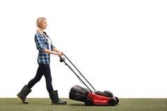 Frau, die einen Rasen mit einem Rasenmäher mäht Stockbild