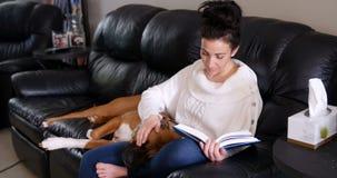 Frau, die einen Roman während Hund sich entspannt auf ihrem Schoss liest stock video footage