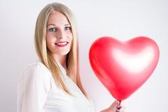 Frau, die einen roten Herzballon hält Stockbild