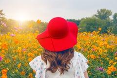 Frau, die einen roten Hut auf einem Gebiet von Blumen trägt Stockfoto