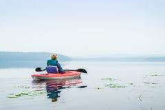Frau, die einen ruhigen See vom Kajak genießt Stockfotografie