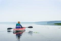 Frau, die einen ruhigen See vom Kajak genießt Lizenzfreie Stockfotos