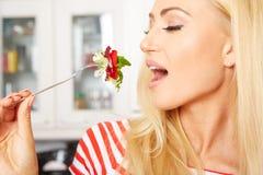 Frau, die einen Salat in ihrer Küche isst Stockfotografie
