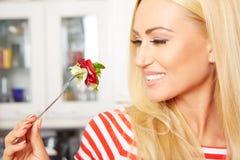 Frau, die einen Salat in ihrer Küche isst Lizenzfreies Stockbild