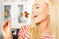 Frau, die einen Salat in ihrer Küche isst Lizenzfreie Stockbilder