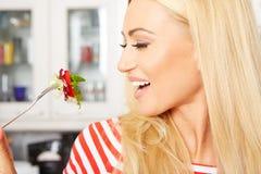 Frau, die einen Salat in ihrer Küche isst Lizenzfreie Stockfotografie