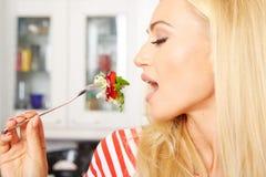 Frau, die einen Salat in ihrer Küche isst Stockbild