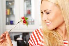 Frau, die einen Salat in ihrer Küche isst Lizenzfreies Stockfoto