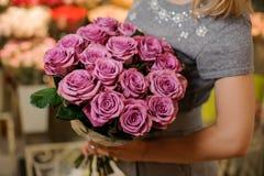 Frau, die einen schönen Blumenstrauß von purpurroten Rosen hält Lizenzfreie Stockfotos