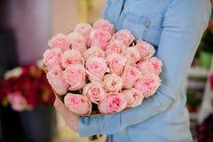 Frau, die einen schönen und zarten Blumenstrauß von rosa Rosen hält Stockfoto