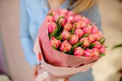 Frau, die einen schönen und zarten Blumenstrauß von rosa Tulpen hält Lizenzfreie Stockfotografie