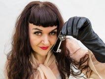 Frau, die einen Schlüssel mit der behandschuhten Hand hält Stockfotografie