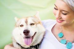 Frau, die einen Schlittenhund hält Lizenzfreie Stockfotos