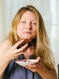 Frau, die einen Schokoladenschokoladenkuchen genießt Lizenzfreie Stockfotografie