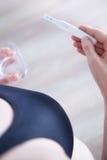Frau, die einen Schwangerschaftstest steht und hält Stockfoto