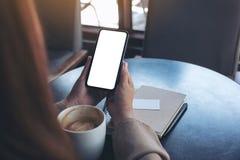 Frau, die einen schwarzen Handy mit leerem Bildschirm für das Aufpassen mit Notizbuch und Kaffeetasse auf Holztisch hält und verw lizenzfreies stockfoto