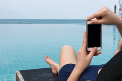 Frau, die einen Smartphone an der Pool- und Seeunschärfe hält Lizenzfreie Stockfotos
