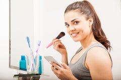 Frau, die einen Smartphone im Badezimmer verwendet Lizenzfreie Stockfotografie
