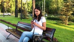 Frau, die einen Smartphone im Park verwendet stock video footage