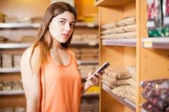 Frau, die einen Smartphone verwendet und Blickkontakt aufnimmt Lizenzfreie Stockfotos