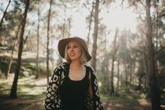 Frau, die einen Spaziergang mitten in einem Kieferwald macht Stockfotografie