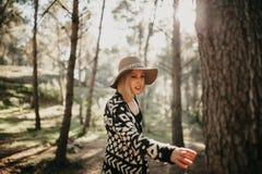 Frau, die einen Spaziergang mitten in einem Kieferwald macht und zu einem Kieferstamm erreicht Lizenzfreies Stockfoto