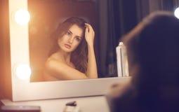 Frau, die einen Spiegel untersucht Stockfoto