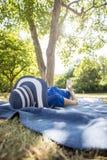 Frau, die einen Strohhut sich entspannt durch das Lügen im Park unter dem tr trägt Lizenzfreie Stockfotografie