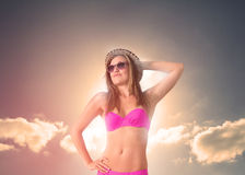 Frau, die einen Strohhut sich entspannt unter der Sonne trägt Stockfotografie
