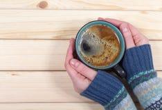 Frau, die einen Tasse Kaffee auf dem hölzernen Hintergrund hält stockfotografie