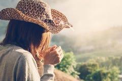 Frau, die einen Tasse Kaffee mit schöner Landschaft hält stockfoto