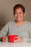 Frau, die einen Tasse Kaffee zu Hause hat Stockbilder